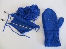 Blau strickte Handschuh und einen unfertigen gestrickten Handschuh Stockbilder