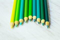 Blau und Grün färbten Bleistifte in Folge auf Weiß Stockfotografie
