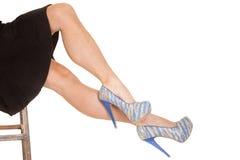 Blau und Sonnenbräune der Frauenschwarzrockbeine heraus auf Schemel. Stockfotos