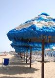 Blau und Weiß eingesäumte Strandschirme Stockfotografie