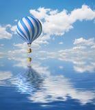 Blau-weißer Heißluft-Ballon im Himmel Lizenzfreie Stockfotografie