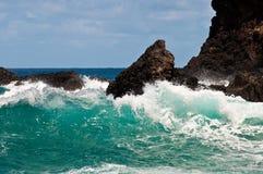 Blau-Wellen, die auf Felsen abbrechen stockfoto