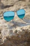 Blau widergespiegelte Sonnenbrille auf dem Strandhintergrundabschluß oben Stockbild