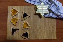 Blaubeer- und Aprikosenstaupl?tzchen Hamantash Purim mit Holztischhintergrund- und David-Sternformkerze stockbild