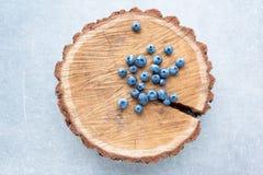Blaubeere auf hölzernem Stumpfhintergrund Reife und saftige frische ausgewählte Blaubeernahaufnahme, Draufsicht Stockfotografie