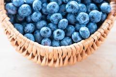 Blaubeere im Korb auf Holztischhintergrund Reife und saftige frische ausgewählte Blaubeernahaufnahme, Draufsicht Lizenzfreies Stockfoto