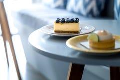 Blaubeeren backen zusammen und Zitronenkuchen auf einer Weinleseplatte lizenzfreies stockbild