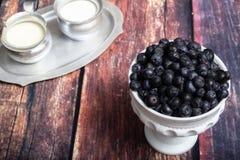Blaubeeren im Milch-Glas-Teller Stockfotos
