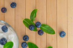 Blaubeeren mit Jogurt- und Minzenblättern auf Holztisch Lizenzfreie Stockbilder