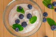 Blaubeeren mit Jogurt- und Minzenblättern auf Holztisch Lizenzfreies Stockbild