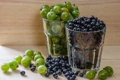 Blaubeeren und Stachelbeeren im Glas mit scatered Beeren Gute Wahl zum Frühstück stockbilder