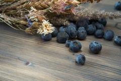 Blaubeeren und trockener Blumenblumenstrauß auf hölzernem Brett Lizenzfreie Stockfotografie
