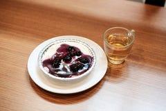 Blaubeerkäsekuchen mit chinesischem grünem Tee und künstliche Anlage auf dem Holztisch stockbilder