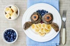 Blaubeerschokoladenpfannkuchen mit Bananen in Form einer Eule Lizenzfreie Stockfotografie