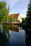 Blaubeuren's Conventual Church. And its reflection in the Blautopf spring pond. Blaubeuren is located near Ulm, South-Germany Royalty Free Stock Images