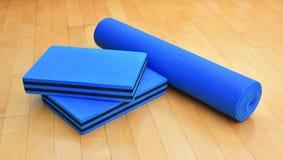 Blaue Übung Matte neben zusammenpassenden Paaren Blöcken für Yoga oder Pil Lizenzfreie Stockbilder