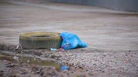 Blaue Abfalltasche der Nahaufnahme mit überschüssigen Lügen nahe Bürgersteig nahe bei Pfütze des Schmutz- und Gummireifens vom Ra stock footage