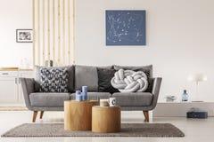 Blaue abstrakte Malerei auf der weißen Wand des zeitgenössischen Wohnzimmers Innen mit grauem Sofa mit Kissen stockfoto