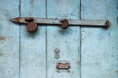 Blaue alte Holztür, zerbröckelnde Farbe, rostiger Metallmist, altes Schloss, Weinlesehintergrund Lizenzfreies Stockfoto