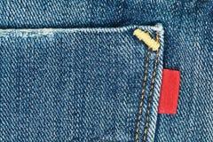 Blaue alte Jeans stecken mit leerem rotem Kennsatz ein Stockbild