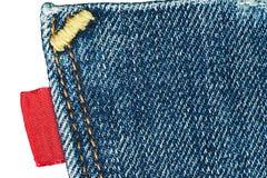 Blaue alte Jeans stecken mit leerem rotem Kennsatz ein Lizenzfreie Stockbilder