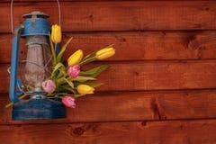 Blaue alte Kerosinlampe mit einem Blumenstrauß von Tulpen auf einem hölzernen Hintergrund Stockbild