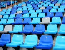 Blaue alte Stadionsplastiksitze auf konkreten Schritten Stockfotos