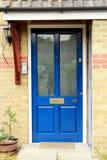 Blaue alte Tür mit orange Bricky Wand Stockfoto
