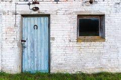 Blaue alte Tür und kleines Fenster einer Sowjet-Ärascheune stockbild