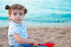 Blaue Augen Brunettekleinkindmädchen, das mit Sand im Strand spielt lizenzfreies stockfoto