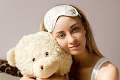 Blaue Augen der Frau mit Schlaf verbinden das Umarmen des Teddybären Stockbilder