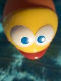 Blaue Augen der Nahaufnahme des gelben Fischplastiks spielen Stockbild