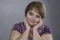 Blaue Augen der schönen älteren Frau Hübscher Erwachsener, der ihr Gesicht berührt stockbild