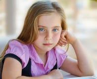 Blaue Augen des blonden entspannten traurigen Kindermädchenausdrucks Stockfoto