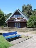 Blaue Bank und altes hölzernes Haus Stockfotografie