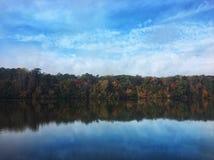 Blaue bewölkte Himmel über dem See mit Reflexionen der Bäume Lizenzfreies Stockfoto
