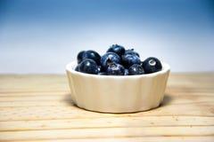 Blaue Blaubeeren auf hölzernem und blauem fon Lizenzfreie Stockfotografie
