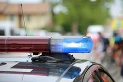 blaue Blinklichter des Polizeiwagens an Sportveranstaltung Stockfotos