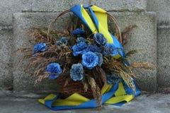 Blaue Blumen mit ukrainischen Staatsflaggen Stockbilder