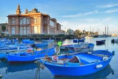 Blaue Boote im adriatischen Meer mit Theater Margherita im Hintergrund Lizenzfreie Stockbilder