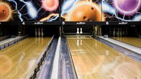 Blaue Bowlingkugel- und weißekegel, die auf einer hölzernen Bowlingbahn, aktives Sportspielkonzept stehen media Blauer Ball stock video