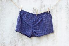 Blaue Boxerunterwäsche auf Schmutzwand Stockfotografie