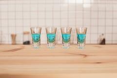 blaue Cocktails in den Schnapsgläsern, die auf Barzähler stehen Lizenzfreie Stockbilder