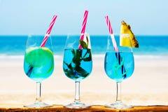 Blaue Cocktails gegen Küstenhintergrund Stockfotografie