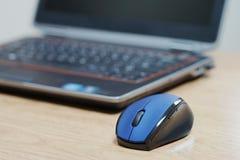 Blaue Computermaus und -laptop lizenzfreie stockfotografie