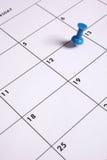 Blaue Daumen-Heftzwecke auf Kalender stockbild