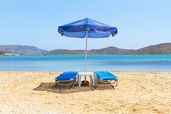 Blaue deckchairs unter Sonnenschirm Stockfotos