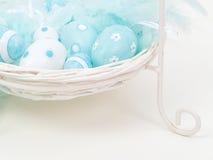 Blaue dekorative Ostereier in einem weißen Korb Stockbild