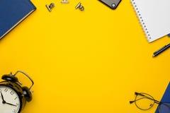 Blaue Einzelteile - ein Notizbuch, ein Wecker, Gläser und Papiere auf einem gelben Hintergrund stockbilder