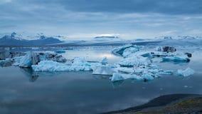 Blaue Eisberge, die unter Mitternachtssonne schwimmen Stockfotos